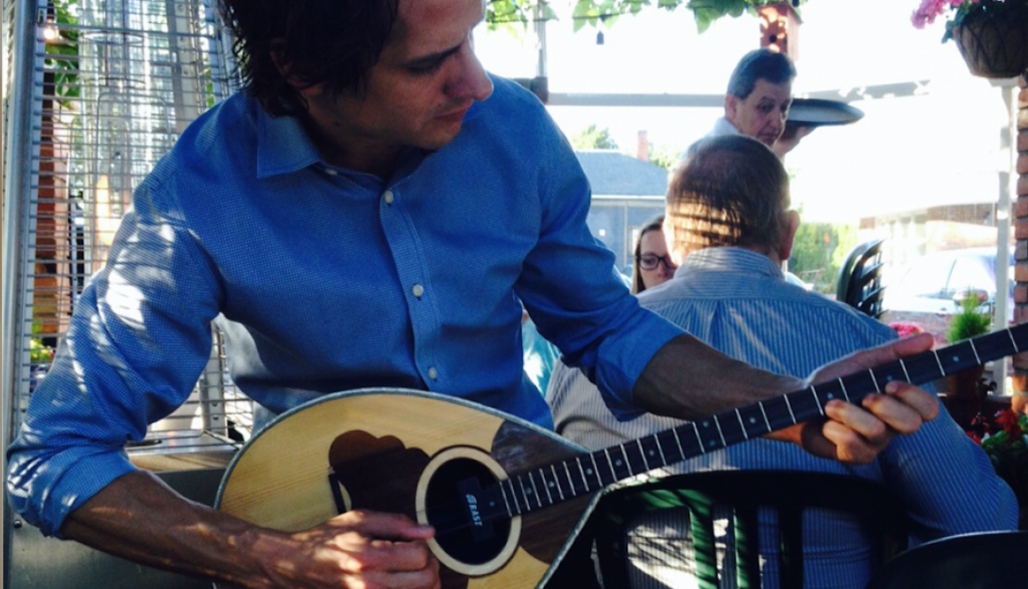 Andreas Adamopoulos plays a bit of bouzouki in between waiting tables.